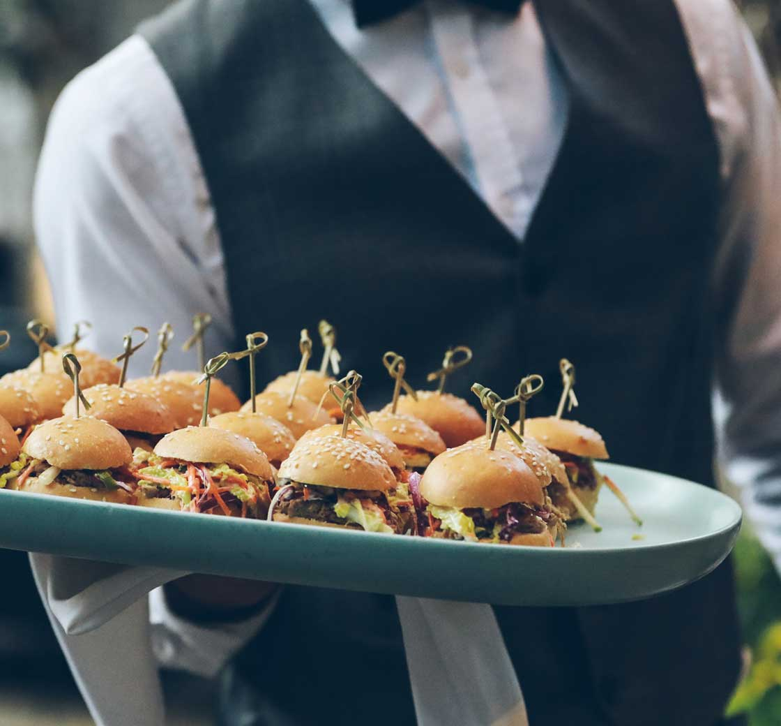 Waiter serves mini burgers as part of our catering service
